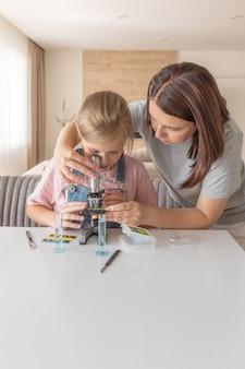 Mãe e filha fazendo alguns experimentos com microscópio em casa