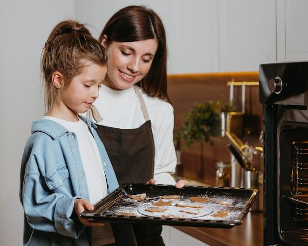 Mãe e filha fazendo biscoitos juntas em casa