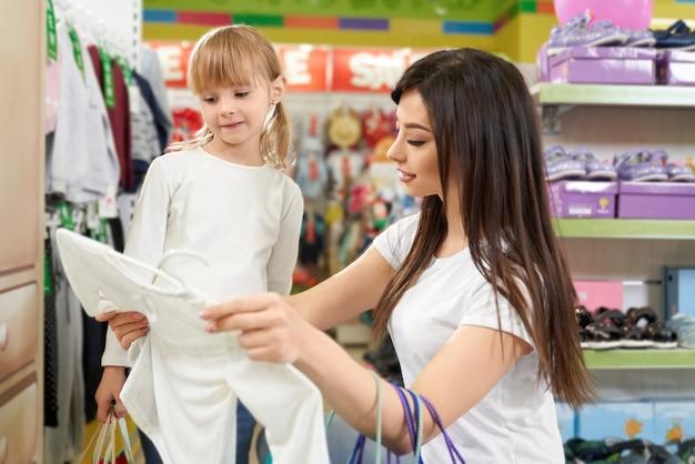 Mãe e filha fazendo compras na boutique com roupas.