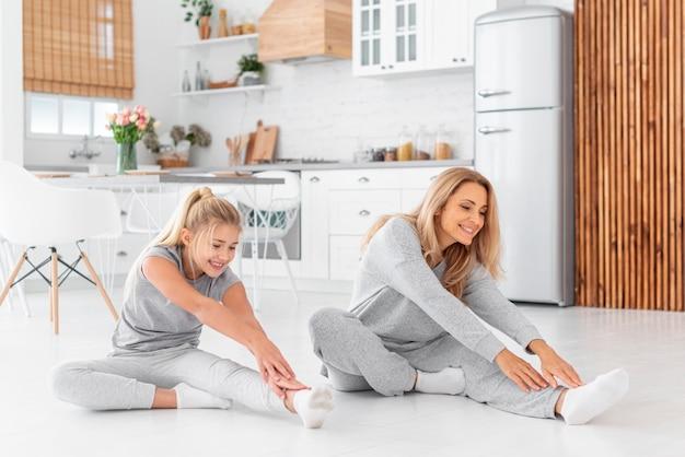 Mãe e filha fazendo exercícios de alongamento