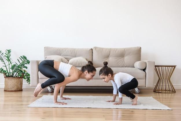 Mãe e filha fazendo exercícios de ioga em casa