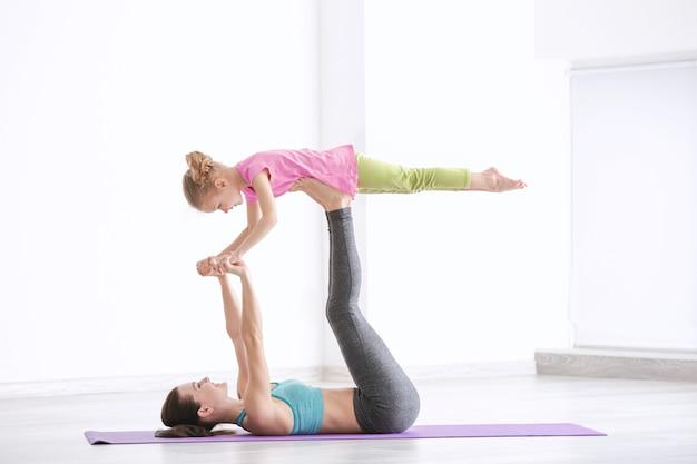 Mãe e filha fazendo exercícios dentro de casa