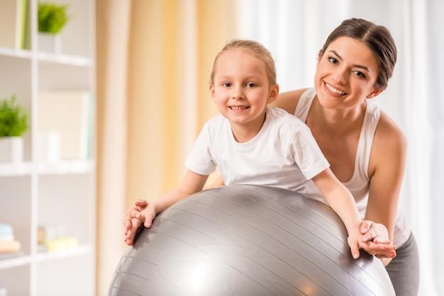 Mãe e filha fazendo exercícios físicos na bola de fitness