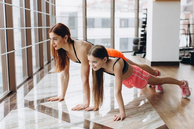 Mãe e filha fazendo flexões no ginásio