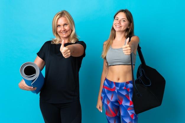 Mãe e filha fazendo ioga fazendo sinal de positivo