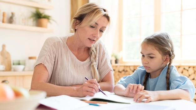 Mãe e filha fazendo lição de casa em casa