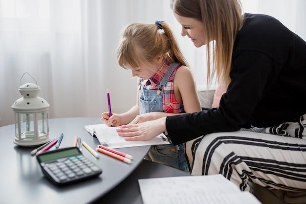 Mãe e filha fazendo lição de casa juntos