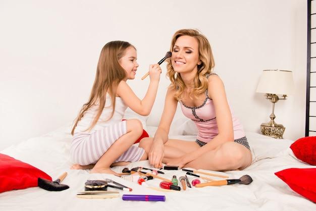 Mãe e filha fazendo maquiagem sentadas na cama no quarto