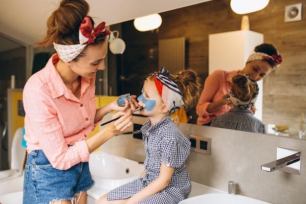 Mãe e filha fazendo máscaras em casa