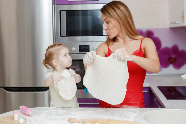 Mãe e filha fazendo massa em casa cozinha