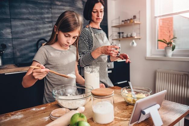 Mãe e filha fazendo massa para torta de maçã