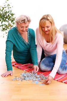 Mãe e filha fazendo quebra-cabeça