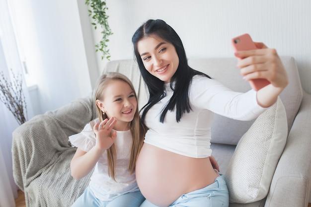 Mãe e filha fazendo selfie juntos.