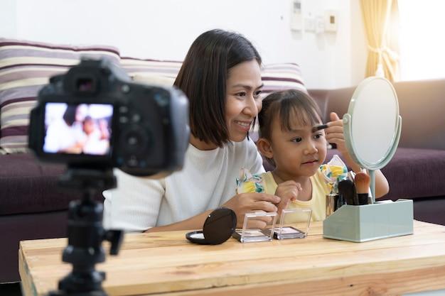 Mãe e filha fazendo sua maquiagem. com gravação fazendo video blogger camera