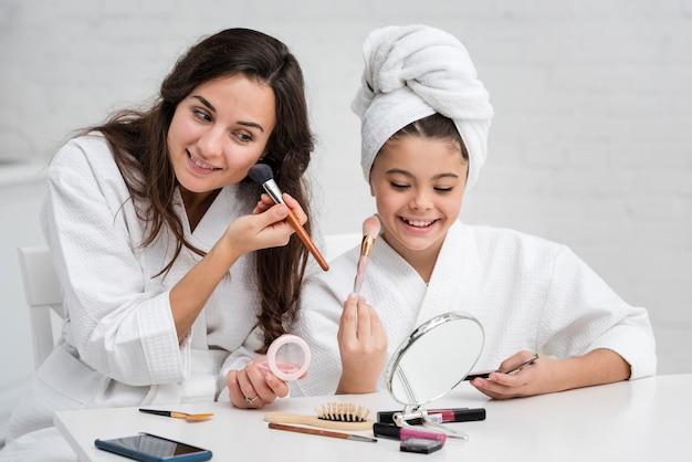 Mãe e filha fazendo sua maquiagem