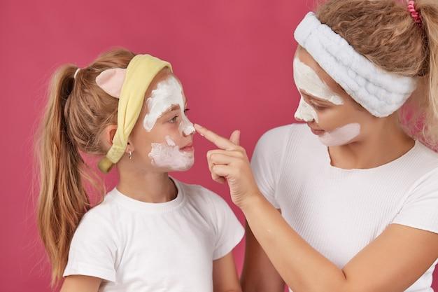 Mãe e filha fazendo uma máscara de argila para o rosto cuidados com a pele da família em um vermelho isolado