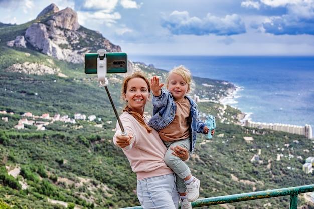 Mãe e filha fazendo uma selfie no fundo de excelentes montanhas de nuvens e o mar a conc ...