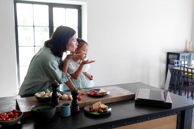 Mãe e filha fazendo uma videochamada da cozinha