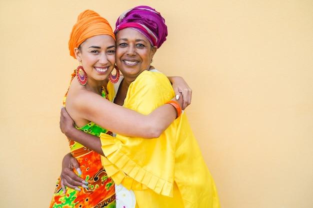 Mãe e filha felizes com os tradicionais vestidos africanos sorrindo - estilo de vida familiar e conceito étnico
