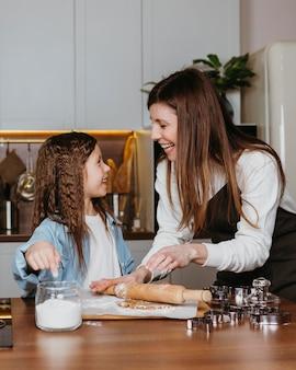 Mãe e filha felizes cozinhando na cozinha de casa