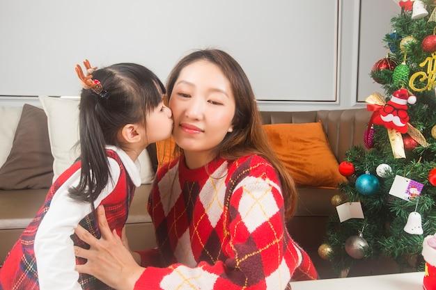 Mãe e filha felizes decorando a árvore de natal e os presentes em casa