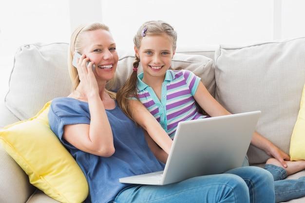 Mãe e filha felizes usando tecnologias no sofá