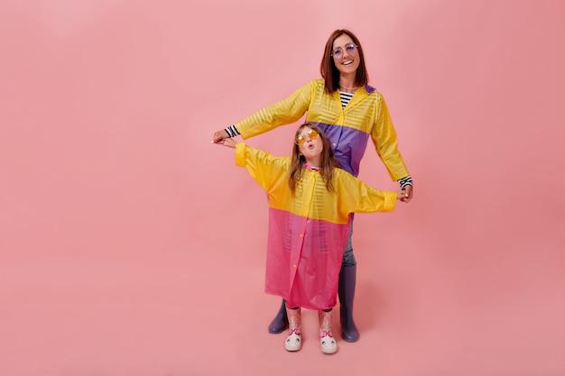 Mãe e filha filha dela vestindo capas de chuva brilhantes. mulher jovem e bonita segurando a filha e sorrindo