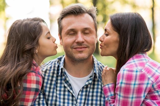 Mãe e filha fofa beijando o pai no parque