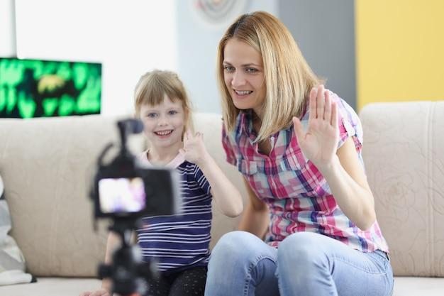 Mãe e filha gravam uma saudação em vídeo para a câmera. blog de vídeo de família. mamãe compartilha sua experiência em criar um filho