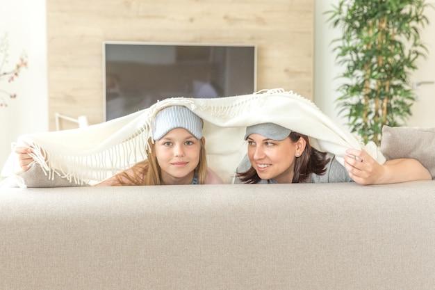 Mãe e filha happ conceito de família, vestindo máscara de dormir e se divertindo no sofá na sala de estar