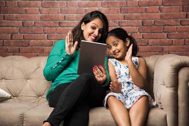 Mãe e filha indiana em videochamada usando computador tablet, acenando com as mãos enquanto está sentada no sofá ou sofá