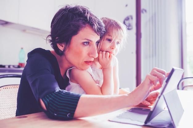 Mãe e filha interior usando tablet