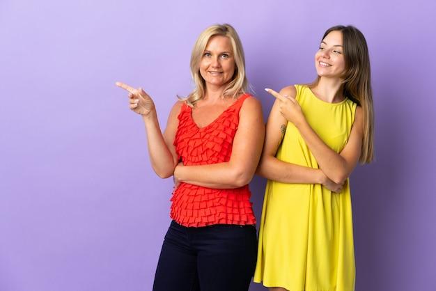 Mãe e filha isoladas em roxo apontando o dedo para o lado na posição lateral