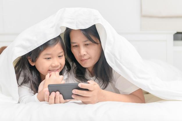 Mãe e filha jogam celular na cama