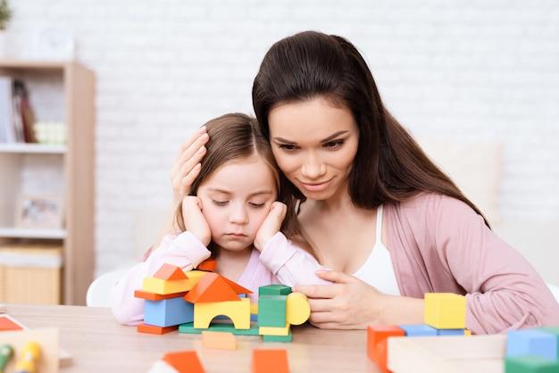 Mãe e filha jogam junto com cubos de madeira.