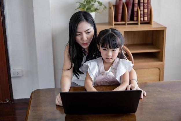Mãe e filha jogando laptop juntos na sala de estar em casa.