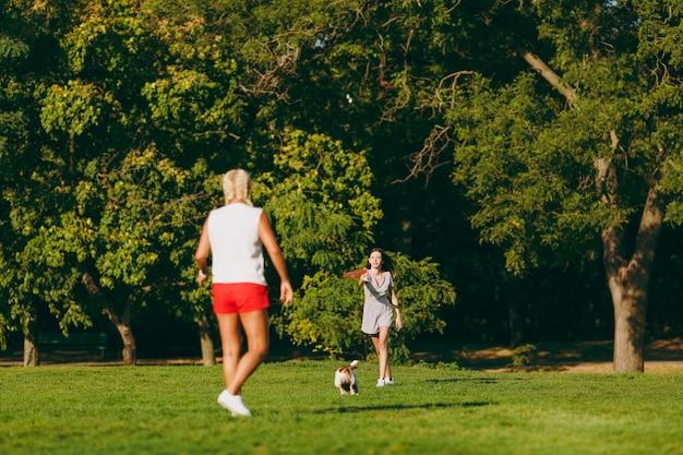 Mãe e filha jogando o disco voador laranja para o pequeno cachorro engraçado, que pegá-lo na grama verde. pequeno animal de estimação jack russel terrier brincando ao ar livre no parque. cachorro e mulheres. família descansando ao ar livre