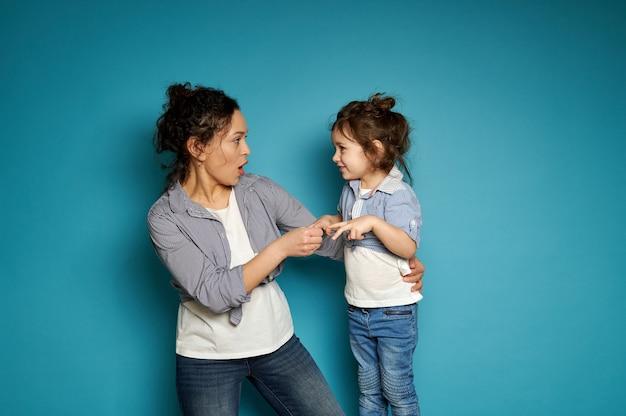 Mãe e filha jogando pedra-papel-tesoura. conceito de maternidade e infância