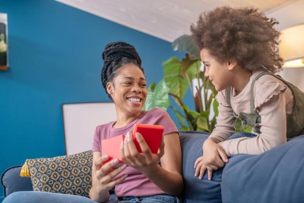 Mãe e filha. jovem e linda mulher afro-americana brilhante com uma caixa vermelha aberta e uma filhinha sorridente carinhosa ao lado do sofá