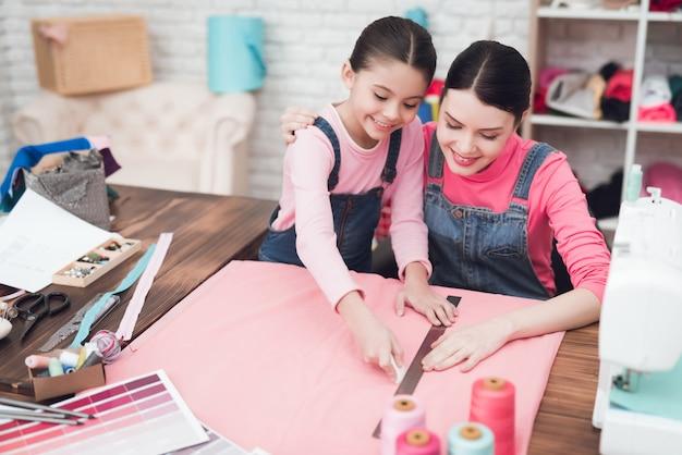 Mãe e filha juntas costuram roupas.