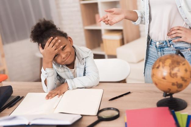 Mãe e filha juntas fazem o dever de casa na escola.