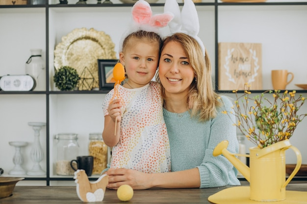 Mãe e filha juntas na cozinha segurando ovos de páscoa