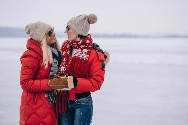 Mãe e filha juntos caminhando no parque no inverno