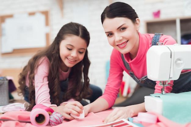 Mãe e filha juntos costurar roupas.