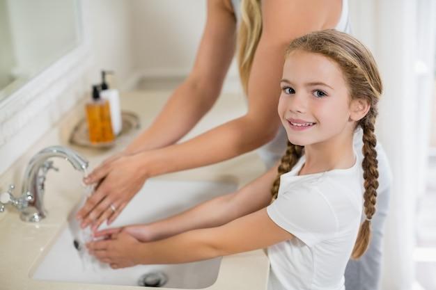 Mãe e filha lavando as mãos na pia do banheiro