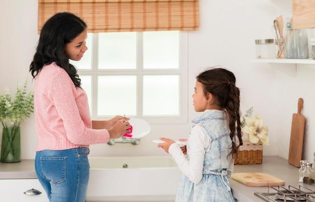 Mãe e filha lavando pratos