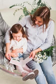 Mãe e filha lendo cartão