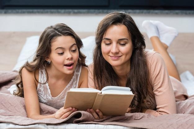 Mãe e filha lendo juntos