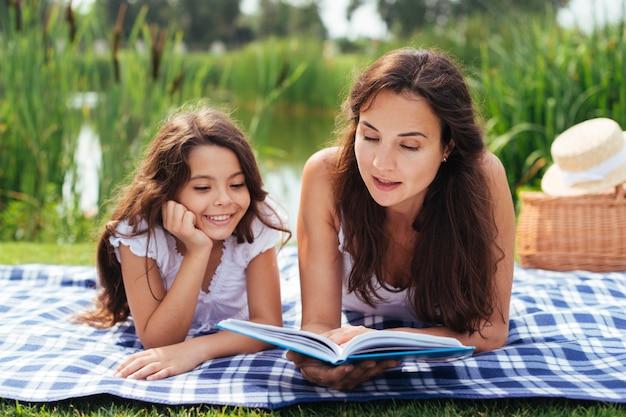 Mãe e filha lendo livro ao ar livre