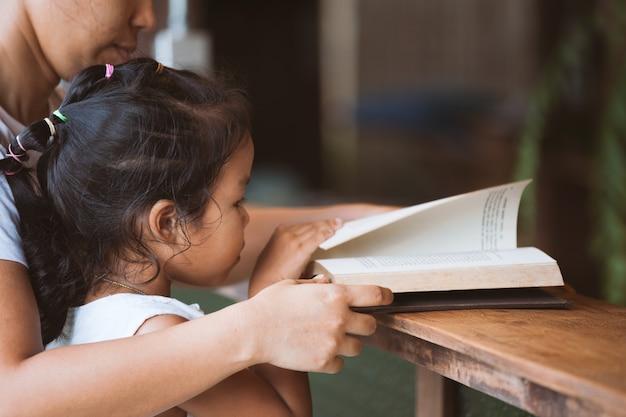 Mãe e filha lendo um livro juntos na casa
